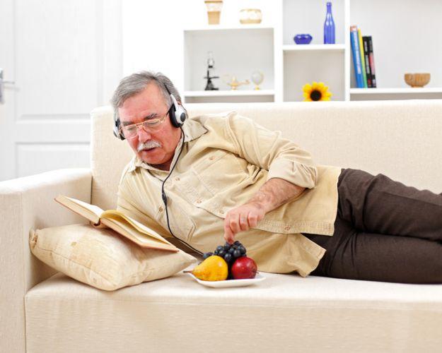 Sénior allongé sur un canapé en train d'écouter de la musique et de manger des fruits