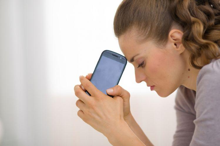 Femme affligée penchée sur son téléphone portable
