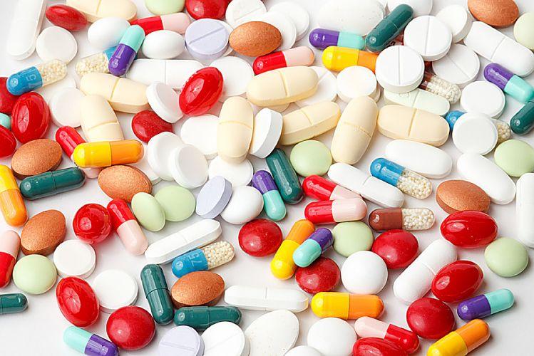 Pilules et cachets de multiples couleurs étalés sur une surface blanche