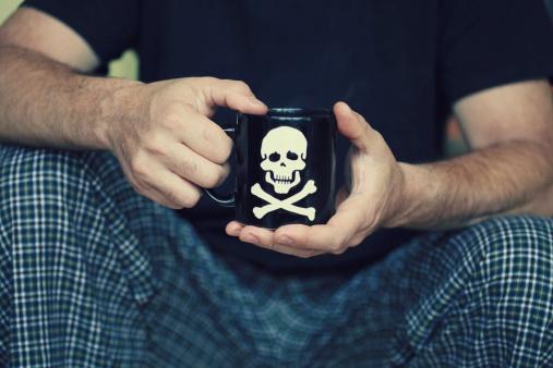 Homme tenant une tasse floquée d'une tête de mort