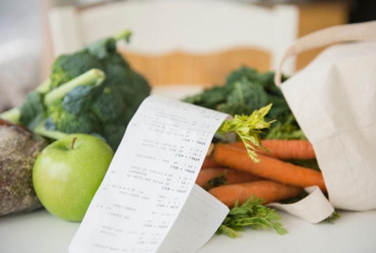 légumes et ticket de caisse sur une table blanche