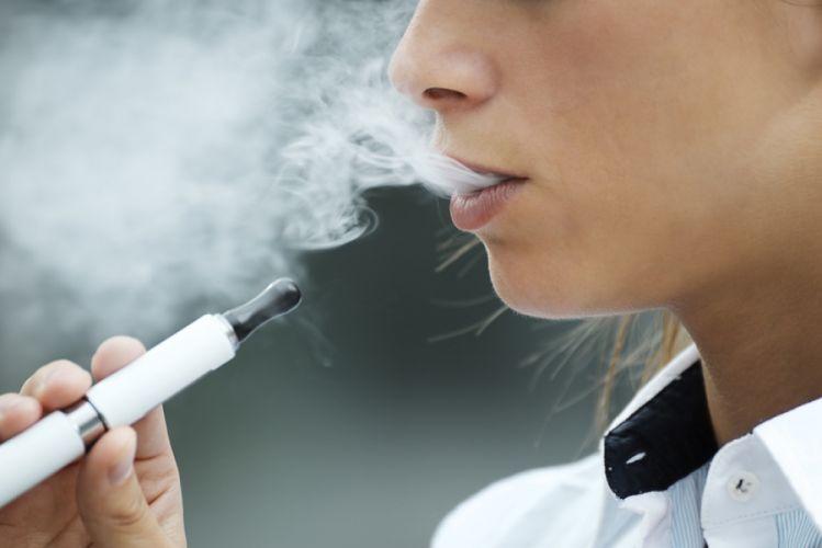 Jeune femme vapotant sur une cigarette électronique