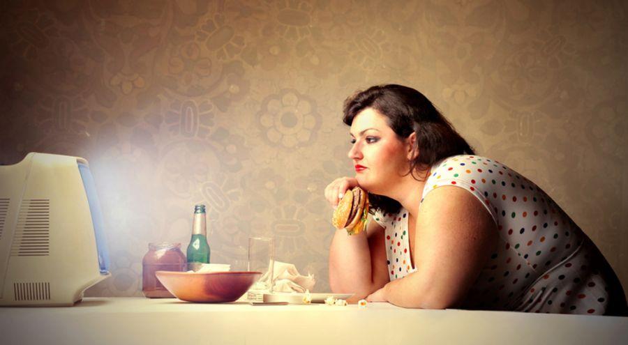 Femme en surpoids mangeant devant son poste de télé