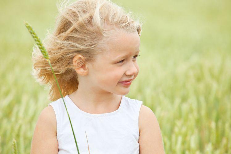 Petite fille blonde dans un champs de blé tenant un épi