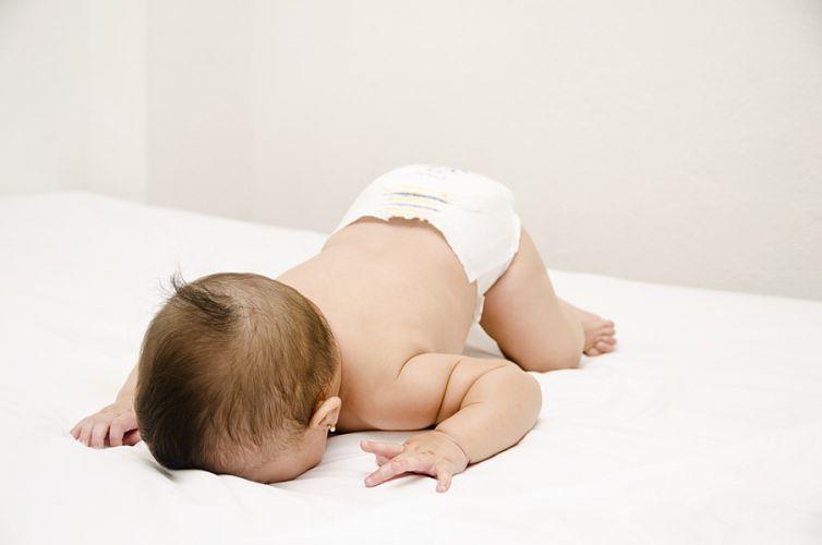 Bébé sur le ventre le visage contre le lit