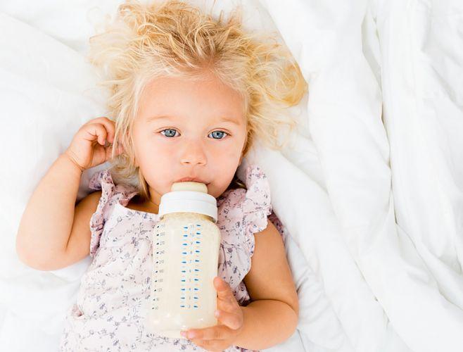 Petite fille blonde prenant son biberon allongée sur un lit