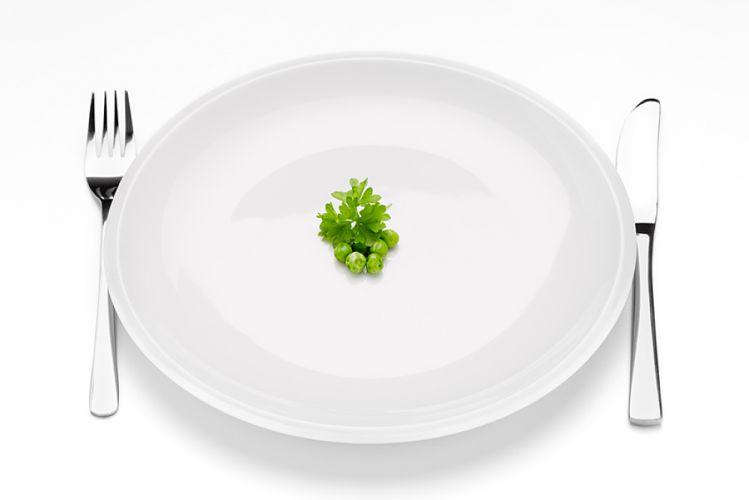 Assiette blanche quasiment vide contenant quelques petits poids et une feuille de persil en son centre