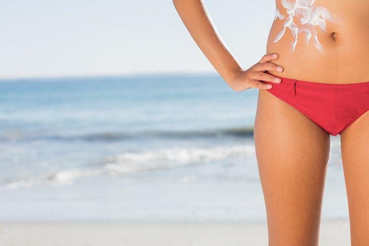 Bas d'un corps de femme debout à la plage en bikini avec un soleil dessiné en crème solaire sur le ventre