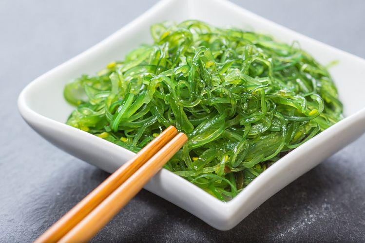 salade d'algues dans une petite soucoupe carrée et baguette en bois