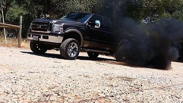 Gros pick-up noir crachant une épaisse fumée noire