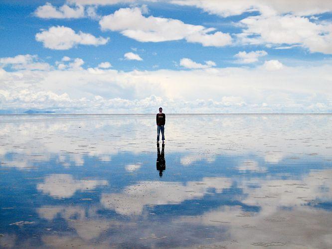 Désert de sable bolivien. Une fine couche d'eau renvoie le reflet d'un homme debout au milieu du paysage