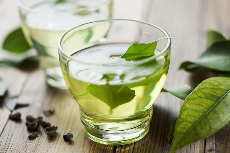 tasse de thé vert, feuilles fraîches et feuilles séchées