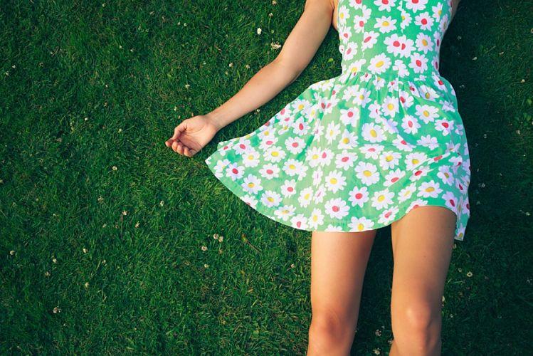 Femme portant une robe à fleur allongée dans l'herbe