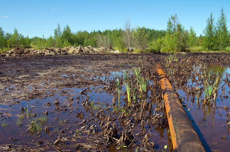 Paysage de campagne pollué par du pétrole échappé d'un oléoduc
