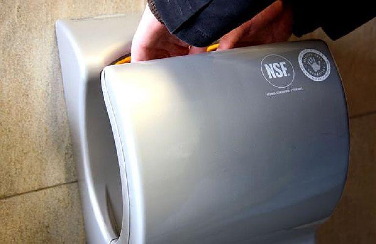 Personne en train de se sécher les mains à l'aide d'un sèche-mains à air pulsé