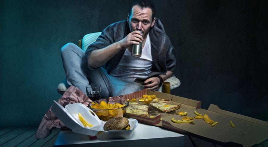 Homme mangeant de la junk food devant sa télé