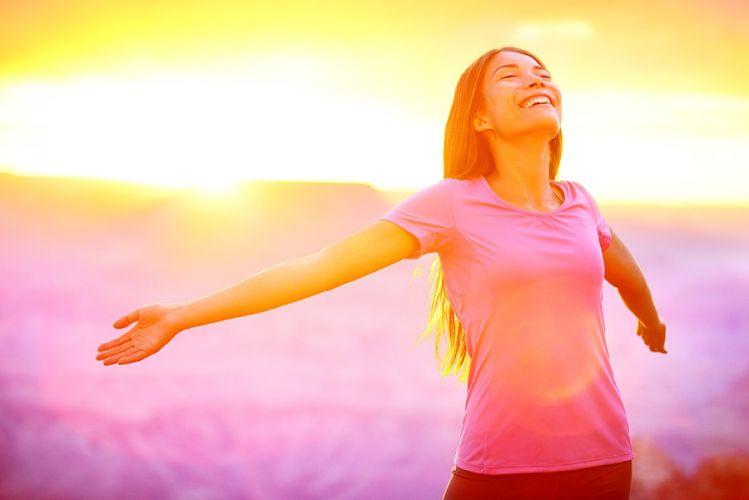 femme ouvrant les bras sur un fond de paysage rose