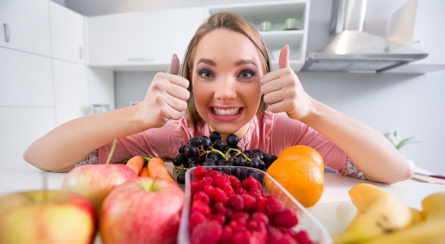 Une femme sourit devant un panier de légume