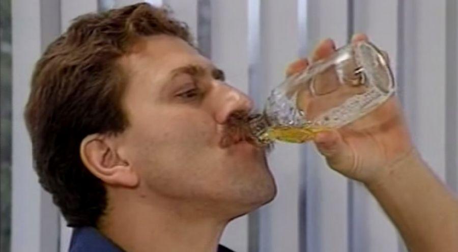 Un homme boit son urine dans un petit bocal