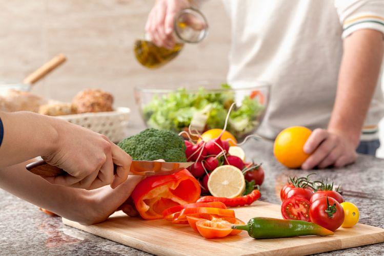 Deux personnes coupant des légumes et assaisonnant une salade