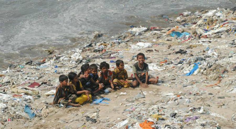 Enfants sur une plage jonchée de déchets