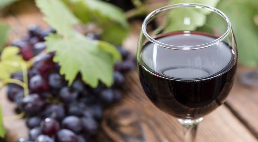 Verre de vin rouge posé sur une table près d'une grappe de raisin