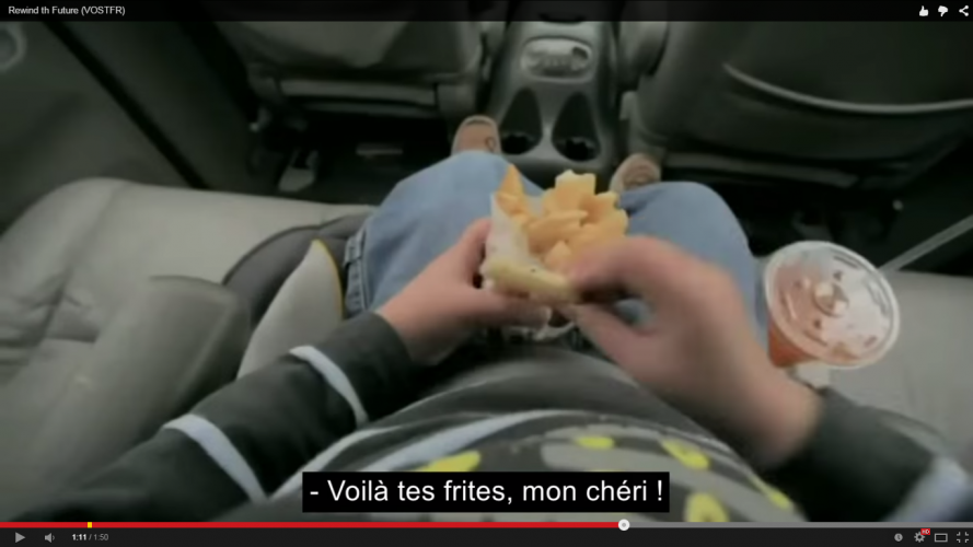 Enfant qui consomme des frites et un soda dans une voiture