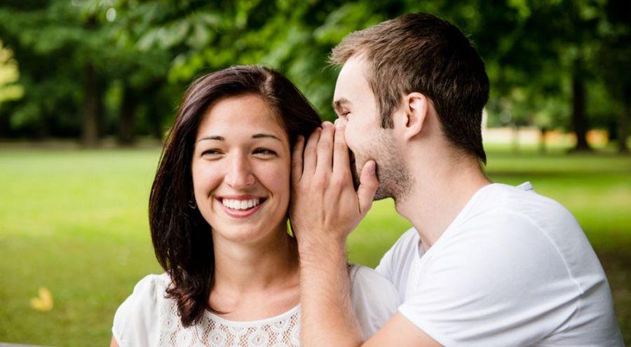 Un homme dit un secret à une femme dans un parc public