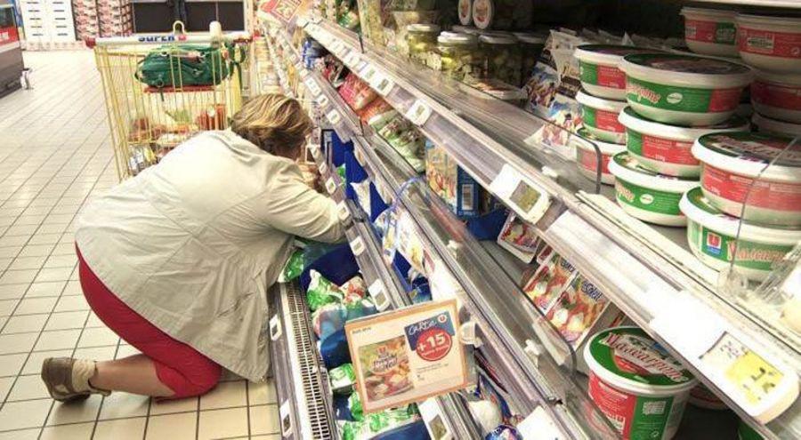 Femme cherchant un produit au fond d'un rayon