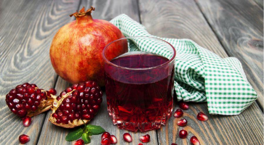 Fruit, graines et verre de jus de grenade posés sur une table en bois