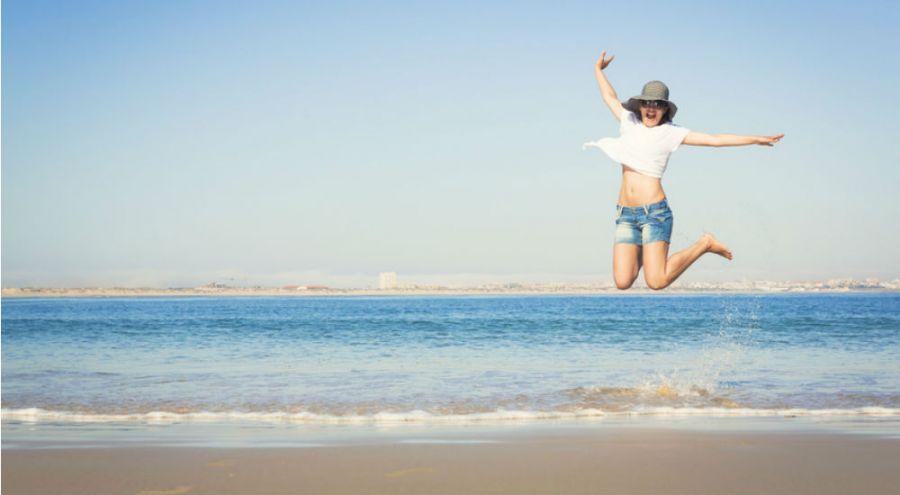 jeune femme qui saute sur la plage