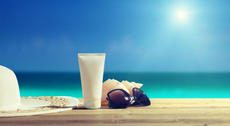 crème solaire lunettes et chapeau de paille à la plage