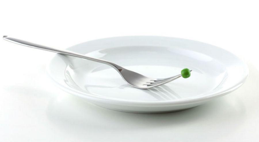Assiette vide et petit pois au bout d'une fourchette