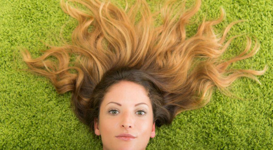 Femme allongée dans l'herbe, les cheveux dispersés