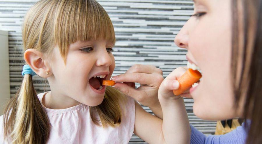 Une petite fille et sa mère se donnent mutuellement à manger une rondelle de carotte