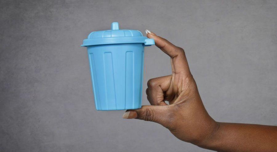 Main présentant une petite poubelle en plastique
