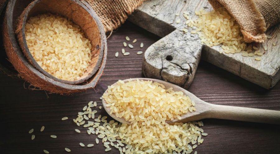 Une cuiller en bois de riz et un bol rempli de cette céréale