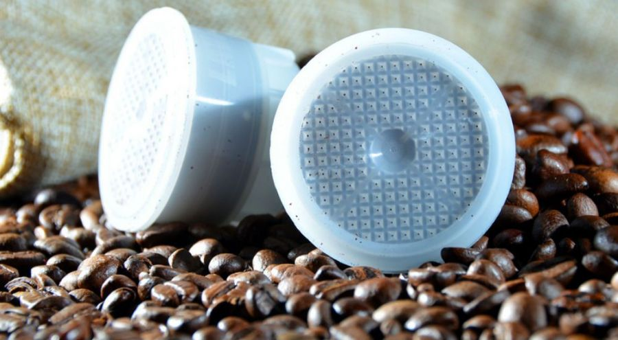 Des grains de café et des capsules de café posées dessus.