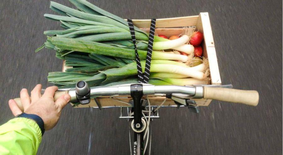 Livraison d'un panier de légumes avec des poireaux à vélo