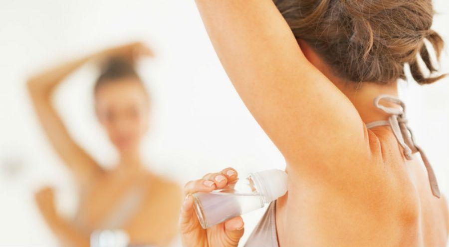 femme de dos qui applique du déodorant à bille face à un miroir