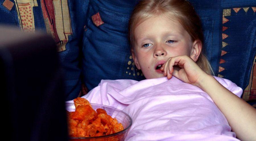 Une fille bourre mange des chips tombes sur le sol du