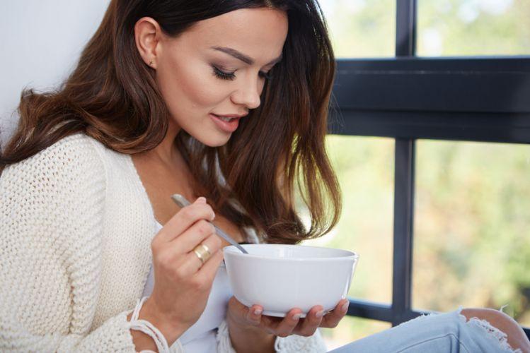 Femme qui mange une soupe dans un bol devant la fenêtre