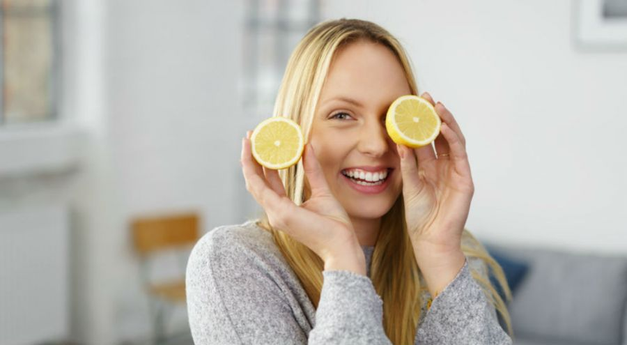 Une femme mince tient deux morceau de citron à la main et fait un clin d'oeil avec l'un des morceaux.