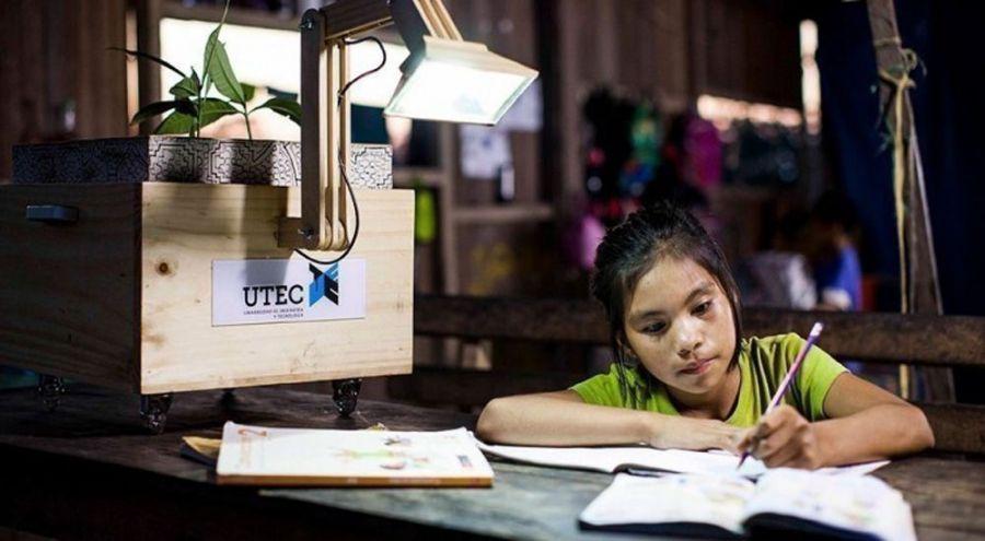 Jeune fille écrit sur un cahier et est éclairé par une lampe à sève