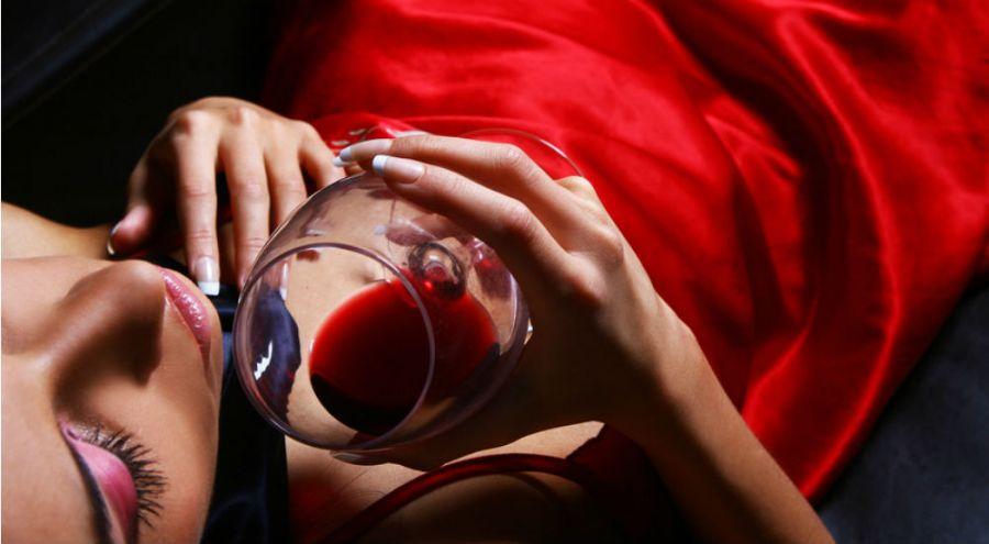 femme en tenue en satin rouge buvant un verre de vinrouge