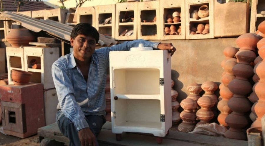 un indien est devant un frigo en argile qui fonctionne sans électricité