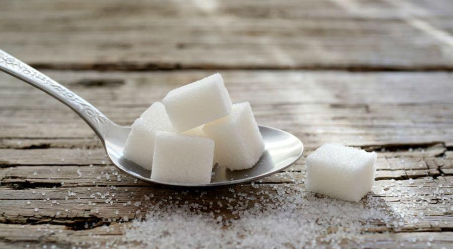 du sucre dans une cuillère à café sur une table en bois