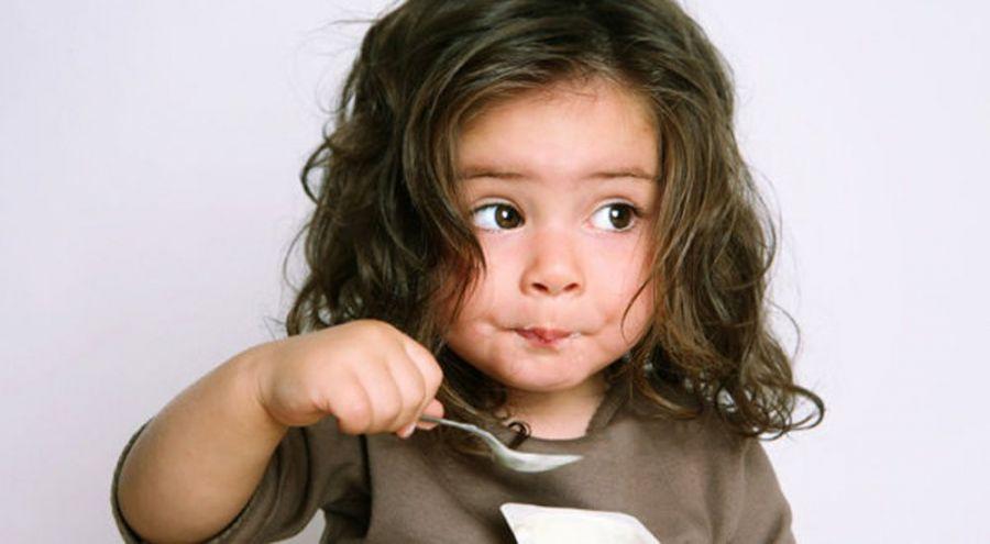 Une jeune fille mange de la soupe à la cuillière