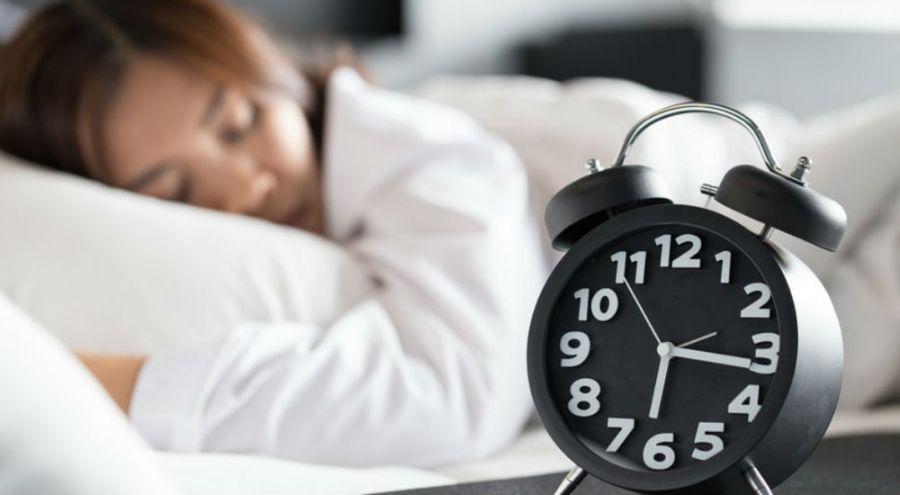 Une femme dort dans lit, devant un réveil est sur la table de chevet