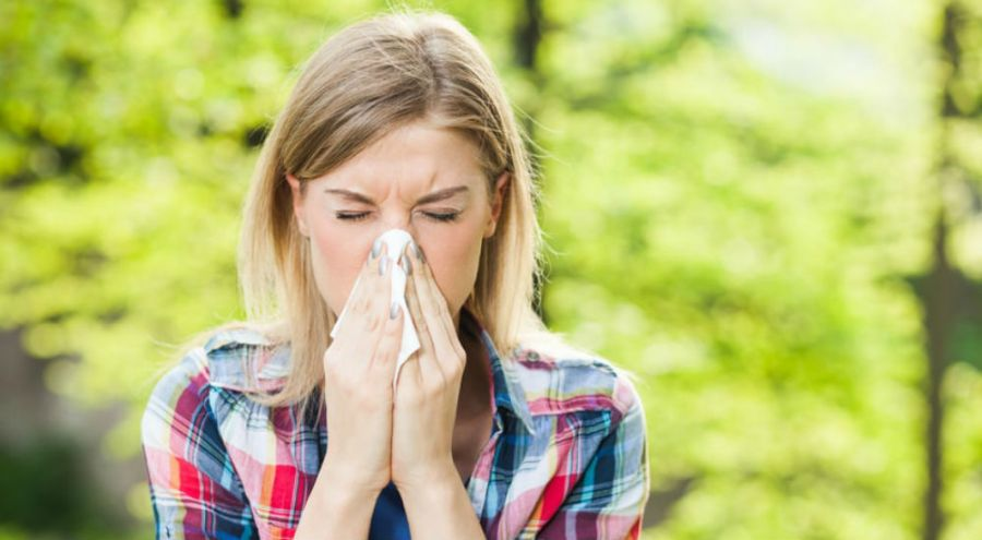 une femme allergique au pollen se mouche